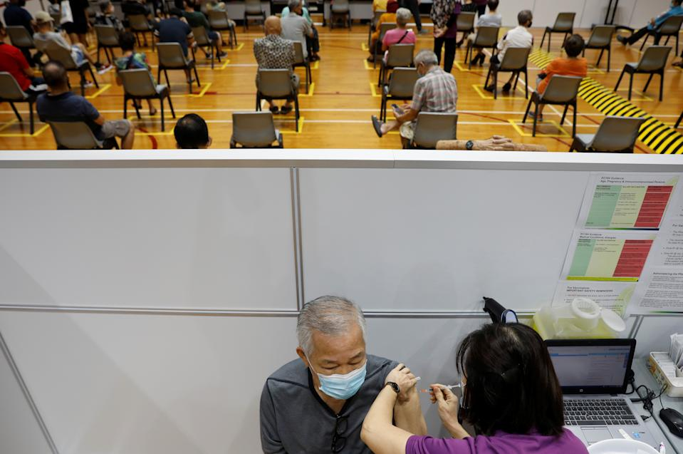 A man receives his vaccination at a coronavirus disease (COVID-19) vaccination center in Singapore March 8, 2021. REUTERS/Edgar Su