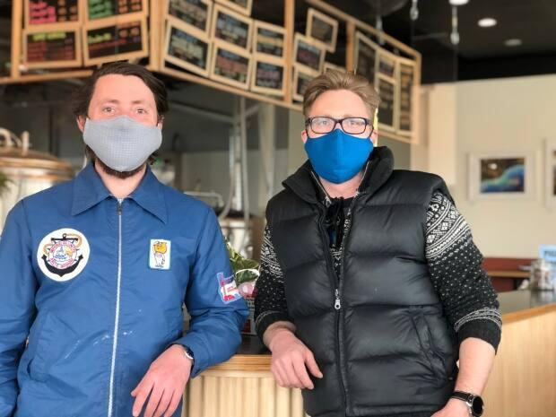 Brothers Kai Miller, left, and Erik Miller, right, own Polarity Brewing in Whitehorse. Kai Miller says he appreciates having the option to open up four more bar seats as of Wednesday, but he adds it wouldn't have much impact on business. (George Maratos/CBC - image credit)