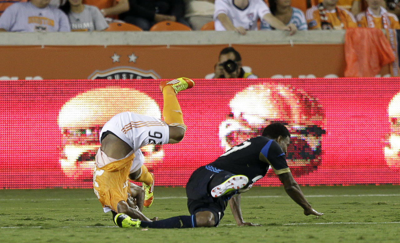 HOUSTON, TX - JUNE 30: Corey Ashe #26 of the Houston Dynamo is upended by Lionard Pajoy #23 of the Philadelphia Union in the second half at BBVA Compass Stadium on June 30, 2012 in Houston, Texas. (Photo by Bob Levey/Getty Images
