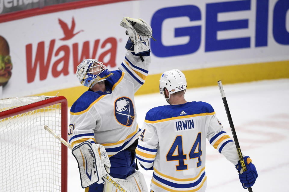 Buffalo Sabres goaltender Dustin Tokarski (31) reacts with defenseman Matt Irwin (44) after the team's NHL hockey game against the Washington Capitals, Thursday, April 15, 2021, in Washington. The Sabres won 5-2. (AP Photo/Nick Wass)