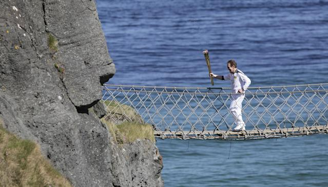 Denis Broderick carries the Olympic Torch over the Carrick-a-Rede rope bridge in county Antrim, Northern Ireland, Monday, June 4, 2012. The Olympic Torch is continuing its relay journey around the country, and is scheduled to arrive at the opening ceremony of the London 2012 Olympic Games. (AP Photo/Peter Morrison)