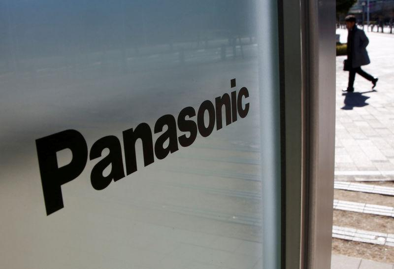 FILE PHOTO - A man is seen next to Panasonic Corp's logo at Panasonic Center in Tokyo