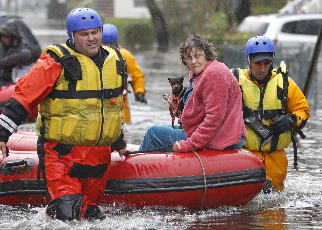 Emergency personnel rescue a resident from flood waters brought on by Hurricane Sandy in Little Ferry, New Jersey, October 30, 2012. Millions of people across the eastern United States awoke on Tuesday to scenes of destruction wrought by monster storm Sandy, which knocked out power to huge swathes of the nation's most densely populated region, swamped New York's subway system and submerged streets in Manhattan's financial district.   REUTERS/Adam Hunger  (UNITED STATES - Tags: DISASTER ENVIRONMENT)