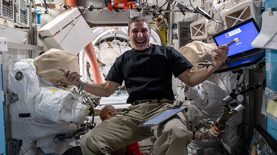 NASA astronaut Mike Hopkins flashes a big smile in a photo posted by the International Space Station on Jan. 21, 2021. The photo shows Hopkins with some other crew members and a pair of spacesuits in the background, surrounded by equipment, working on science experiments and training for an upcoming pair of spacewalks.