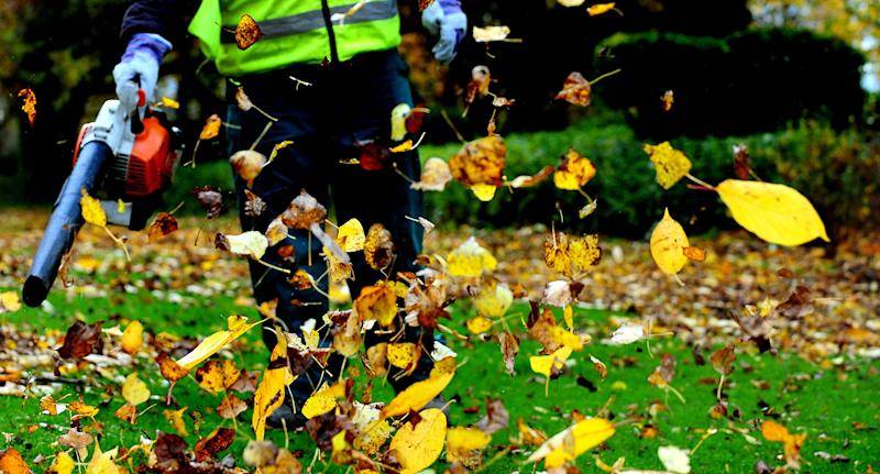 A worker clears leaves with a leaf blower in Swadlincote, south Derbyshire during autumn.