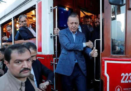 FILE PHOTO - Turkish President Erdogan gets off a vintage tram at Taksim Square in central Istanbul