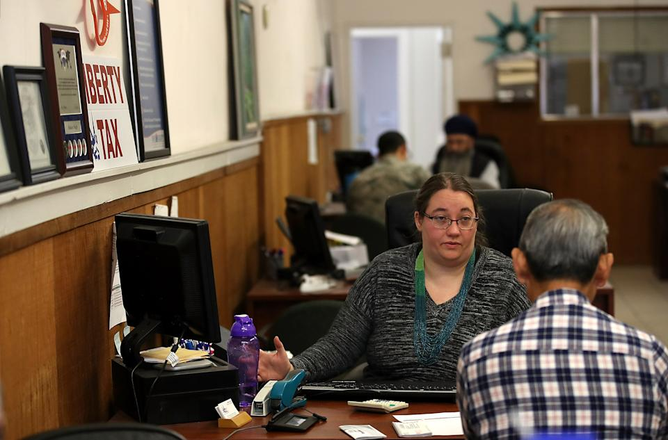 Liberty Tax Service tax specialist Laura Tuuri (C) helps a client do his taxes on April 16, 2018 in Oakland, California. (Photo: Justin Sullivan/Getty Images)