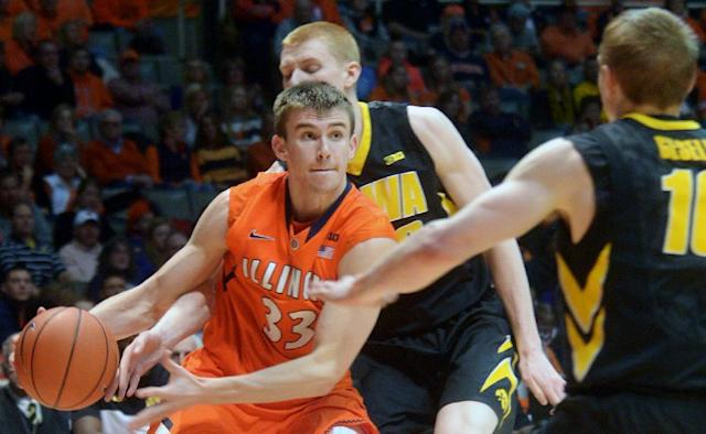 Illinois' Jon Ekey (33) drives between Iowa guard Mike Gesell (10) and Aaron White (30) during an NCAA college basketball game in Champaign, Ill., Saturday, Feb. 1, 2014. (AP Photo/Robin Scholz)