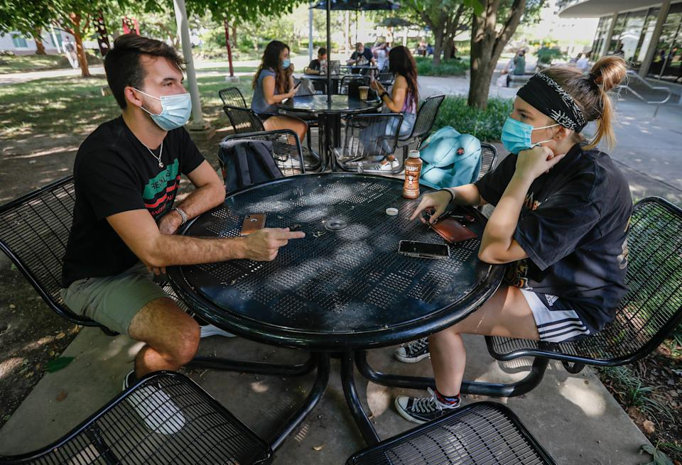 Junior Corbin Blanch, left, and senior Heather Ritter, both wildlife biology majors, talk outside of the Plaster Student Union during the first day of classes at Missouri State University on Monday, Aug. 17, 2020. Precautions like requiring that face masks be worn were implemented to help protect students and staff from spreading COVID-19.