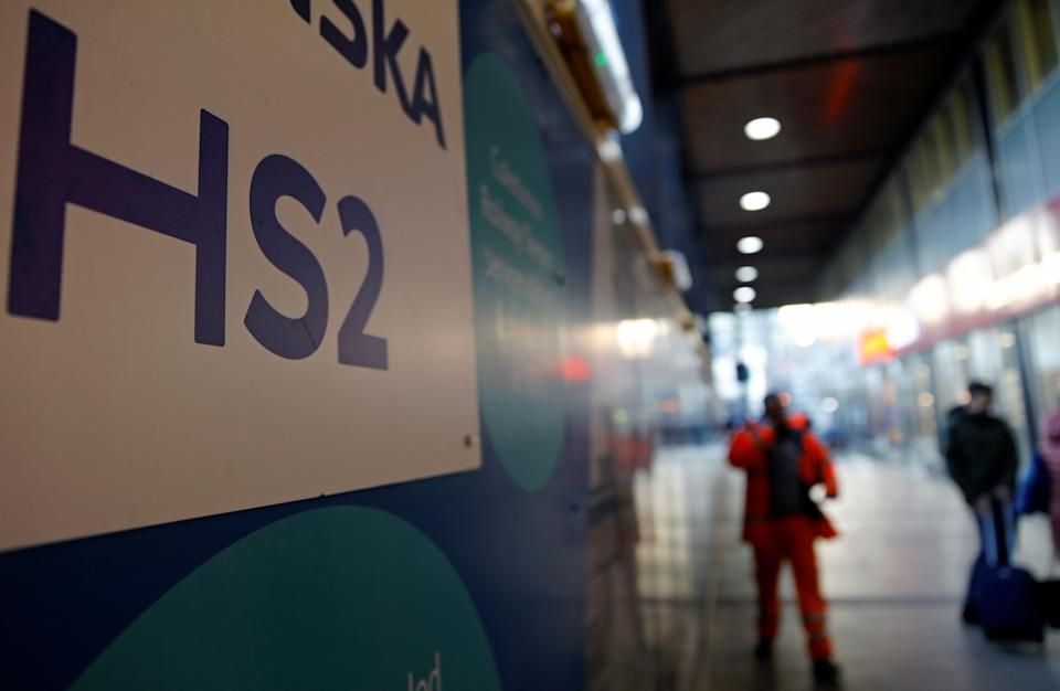 Workers walk past a sign outide a construction site for a section of Britain's HS2 high-speed two railway project, at London Euston train station in London on January 20, 2020. - Britain's government on Monday said it would shortly decide on whether to proceed with its HS2 high-speed two railway project, whose cost is reportedly set to soar to more than £100 billion. HS2, which will quicken rail journeys between London in southeast England and cities to the north of the capital, has been dogged by controversy owing to projected spiralling costs and damage to wildlife. (Photo by Tolga AKMEN / AFP) (Photo by TOLGA AKMEN/AFP via Getty Images)
