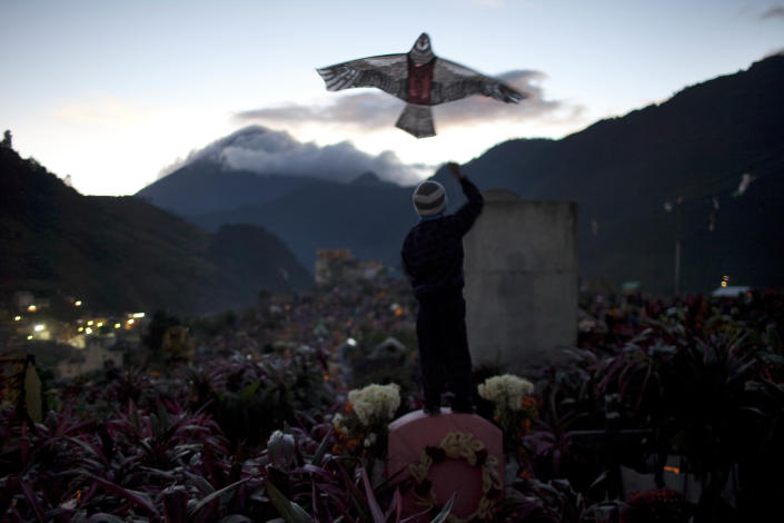 A boy flies a kite in the cemetery on Day of the Dead in Zunil, Guatemala, Tuesday Nov. 1, 2011. Because Mayans believe the dead are allowed to visit their families on earth for one day, family members fly kites to guide their departed relatives to their earthly homes. Also decorating graves with fresh flowers is common throughout Latin America, as is having a picnic at the departed relative's grave site. (AP Photo/Rodrigo Abd)