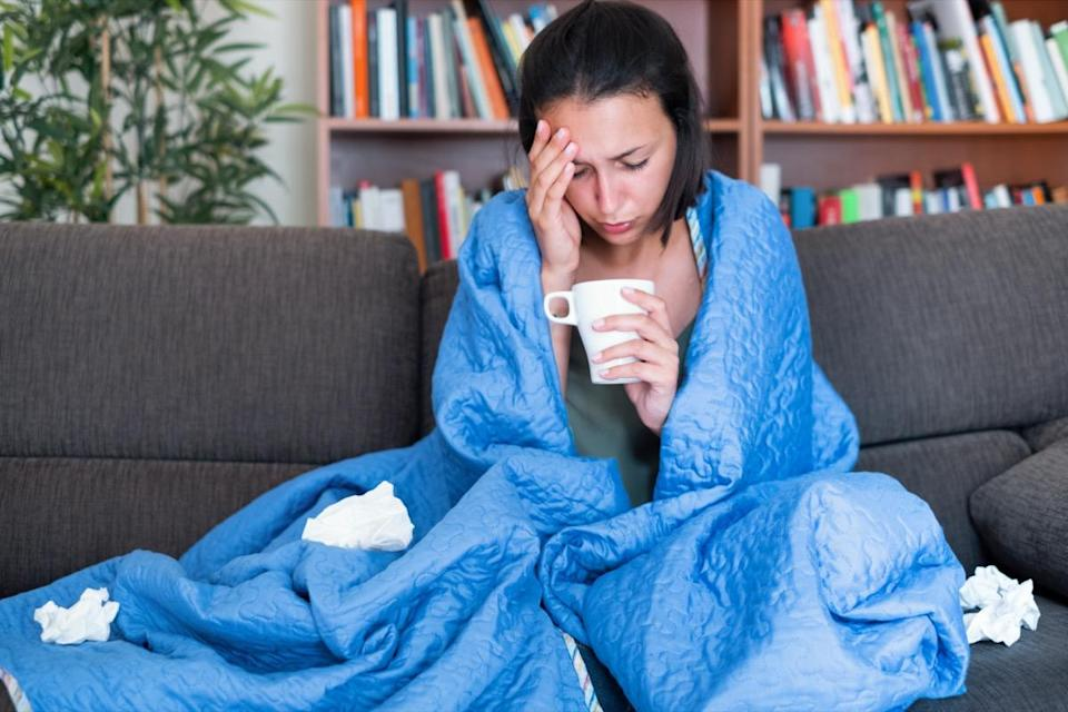 woman covered by a blanket on the sofa with high fever and flu