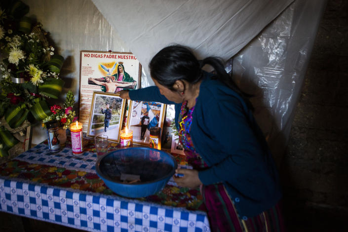 Natalia Tomas places a photo of her son on an altar in her home in in Comitancillo, Guatemala, Wednesday, Jan. 27, 2021. She believes that her son is one of the charred corpses found in a northern Mexico border state on Saturday. The country's Foreign Ministry said it was collecting DNA samples from a dozen relatives to see if there was a match with any of the bodies. (AP Photo/Oliver de Ros)