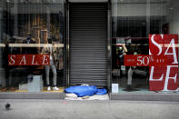 A homeless person sleeps in the doorway of a closed shop on Oxford Street in London, Saturday, Dec. 26, 2020. London is currently in Tier 4 with all non essential retail closed and people have been asked to stay at home, on what is usually one of the busiest retail days of the year with the traditional Boxing Day sales in shops. (AP Photo/Kirsty Wigglesworth)