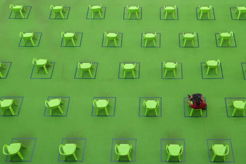 A man sits on a chair marked out to keep social distancing amid the COVID-19 pandemic on March 19, 2021 in Singapore. (Photo by Suhaimi Abdullah/NurPhoto via Getty Images)