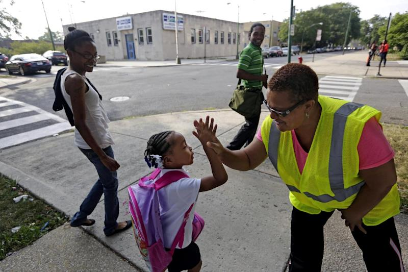 "Safety Guard Renee Green high-fives Demari Hill, 5, as she heads to Gresham Elementary School with her parents Destiny and Anthony Hill on her first day of kindergarten classes on Monday, Aug. 26. 2013, in Chicago. Thousands of students will walk newly designated ""Safe Passage"" routes after CPS announced in May it would close about 50 schools and programs. Workers hired to help students get to and from school safely will be stationed along those routes, as well as police, firefighters and even public library security guards. (AP Photos/M. Spencer Green)"