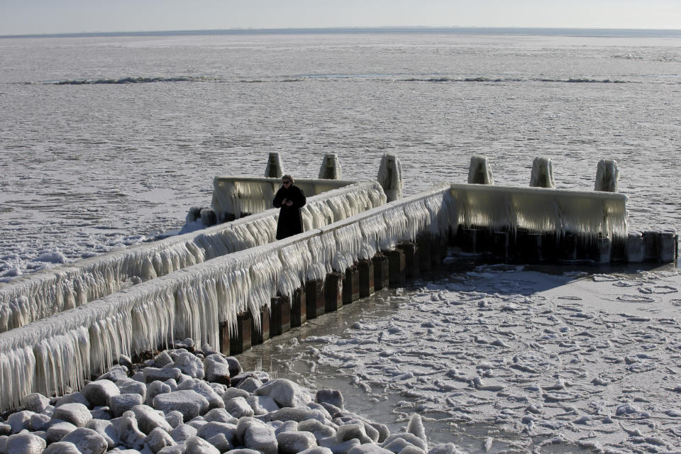 A woman takes pictures of icicles on a jetty at the Afsluitdijk, a dike separating IJsselmeer inland sea, and the Wadden Sea, Netherlands, Thursday, Feb. 11, 2021. The deep freeze gripping parts of Europe served up fun and frustration with heavy snow cutting power to some 37,000 homes in central Slovakia. (AP Photo/Peter Dejong)