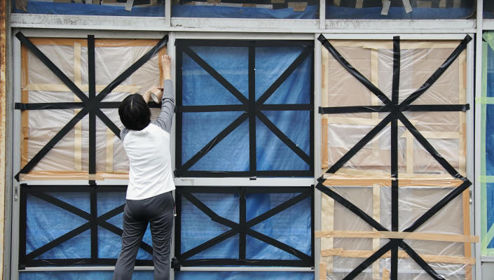 A woman takes windows in preparation for Typhoon Hagibis, in Kyonan town, Chiba prefecture, near Tokyo Friday, Oct. 11, 2019. A powerful typhoon is forecast to bring up to 80 centimeters (31 inches) of rain and damaging winds to the Tokyo area and Japan's Pacific coast this weekend, and the government is warning residents to stockpile necessities and leave high-risk places before it's too dangerous. (Naoya Osato/Kyodo News via AP)