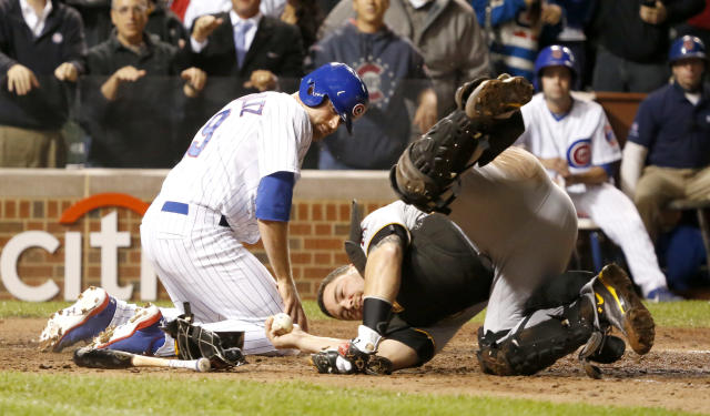 Pittsburgh Pirates catcher Russell Martin holds onto the ball after tagging out Chicago Cubs' Nate Schierholtz during the ninth inning of a baseball game Monday, Sept. 23, 2013, in Chicago. The Pirates won 2-1. (AP Photo/Charles Rex Arbogast)