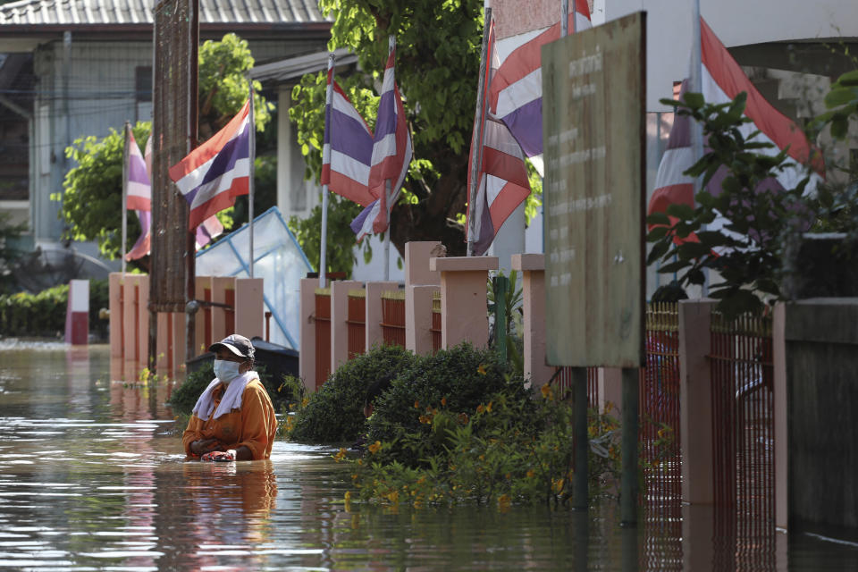 A woman wades through floodwaters in Ayutthaya province, north of Bangkok, Thailand, Monday, Oct. 4, 2021. As flood waters continued to inundate areas in northern and central Thailand and were starting to hit low-lying areas in the capital, Thai officials were looking warily ahead Tuesday the possibility of more storms this month, but were optimistic the devastation of a decade ago would not be repeated. (AP Photo/Nathathida Adireksarn)