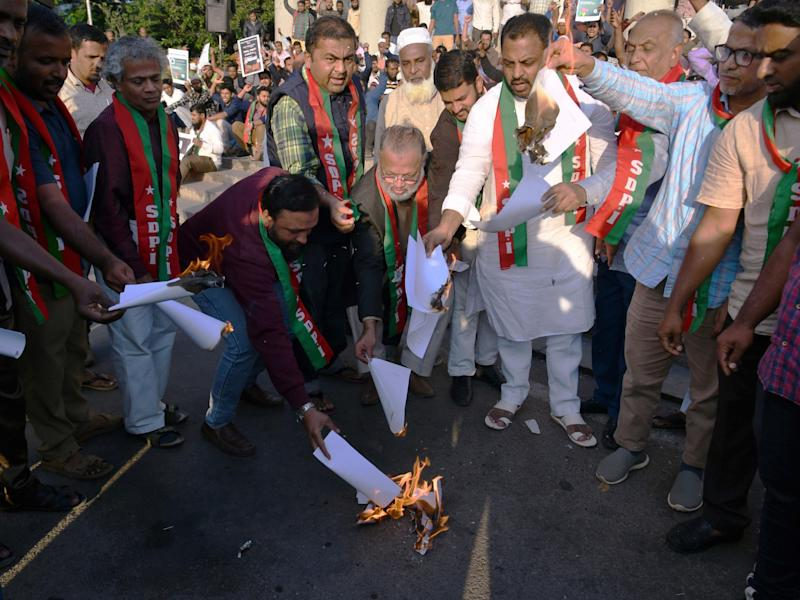Members and activists shout slogans against the Indian government as they burn copies of the Citizenship Amendment Bill 2019: AFP via Getty Images