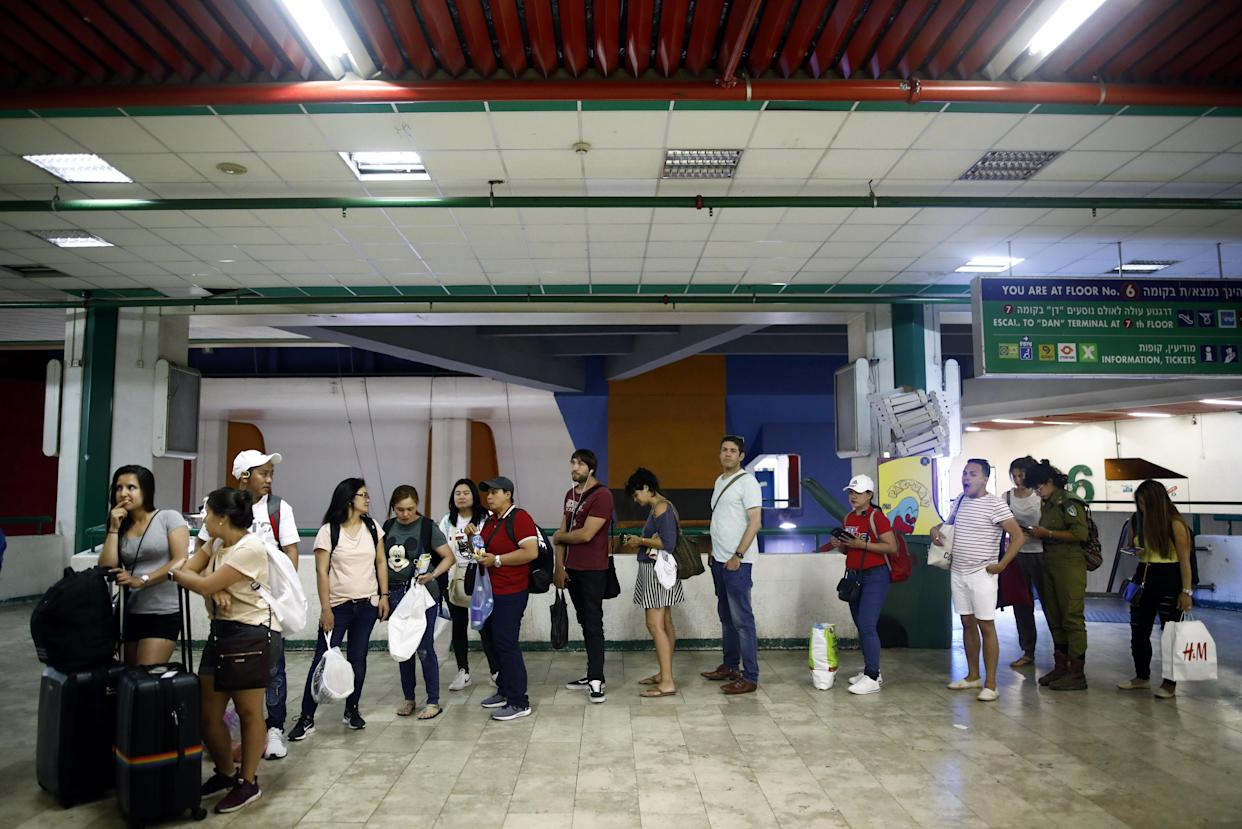 Passengers wait to board a bus at the Central Bus Station on May 25. (Photo: Corinna Kern/Reuters)