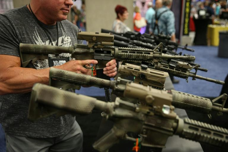 A man inspects a firearm at the NRA convention