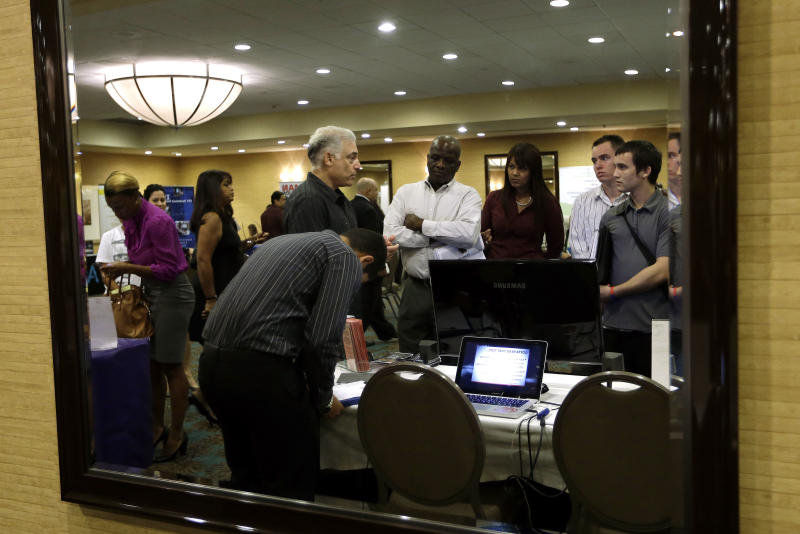 FILE - In this Monday, Sept 17, 2012, file photo, Robert Orkin of the company TxT-Alert, third from left, talks with job seekers during a job fair held by National Career Fairs in Fort Lauderdale, Fla. The U.S. unemployment rate fell to 7.8 percent last month, dropping below 8 percent for the first time in nearly four years. (AP Photo/Lynne Sladky, File)