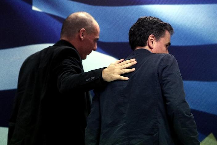 Outgoing Finance Minister Yanis Varoufakis (L) places his hand on the shoulder of newly appointed Greek Finance Minister Euclid Tsakalotos during a handover ceremony at the Finance Ministry in Athens on July 6, 2015 (AFP Photo/Angelos Tzortzinis)