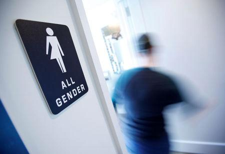 FILE PHOTO - A bathroom sign welcomes both genders at the Cacao Cinnamon coffee shop in Durham North Carolina
