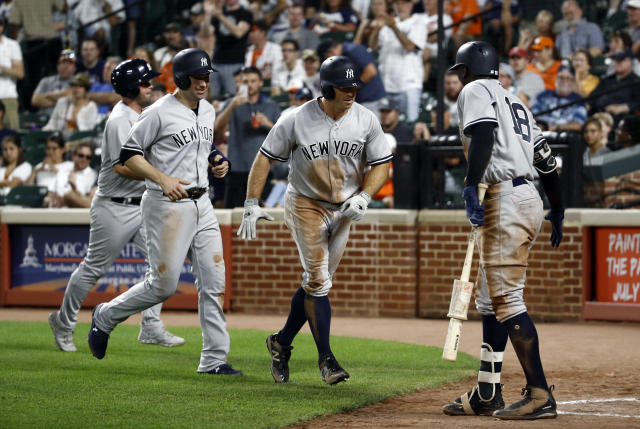 New York Yankees' Brett Gardner, second from right, and Neil Walker, second from left, greet teammate Didi Gregorius (18) after Gardner batted in Walker on a home run in the fourth inning of the second baseball game of a doubleheader against the Baltimore Orioles, Monday, July 9, 2018, in Baltimore. (AP Photo/Patrick Semansky)