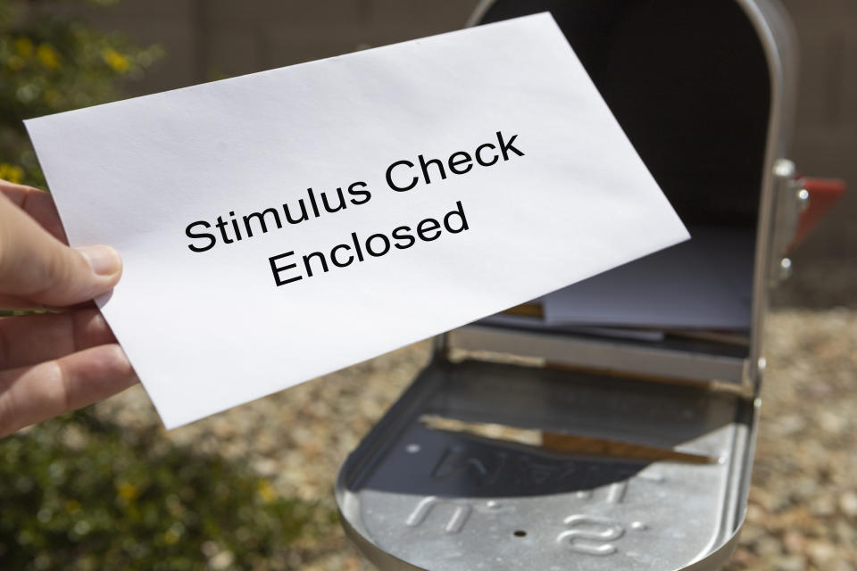 A person retrieves their stimulus check from the mailbox.