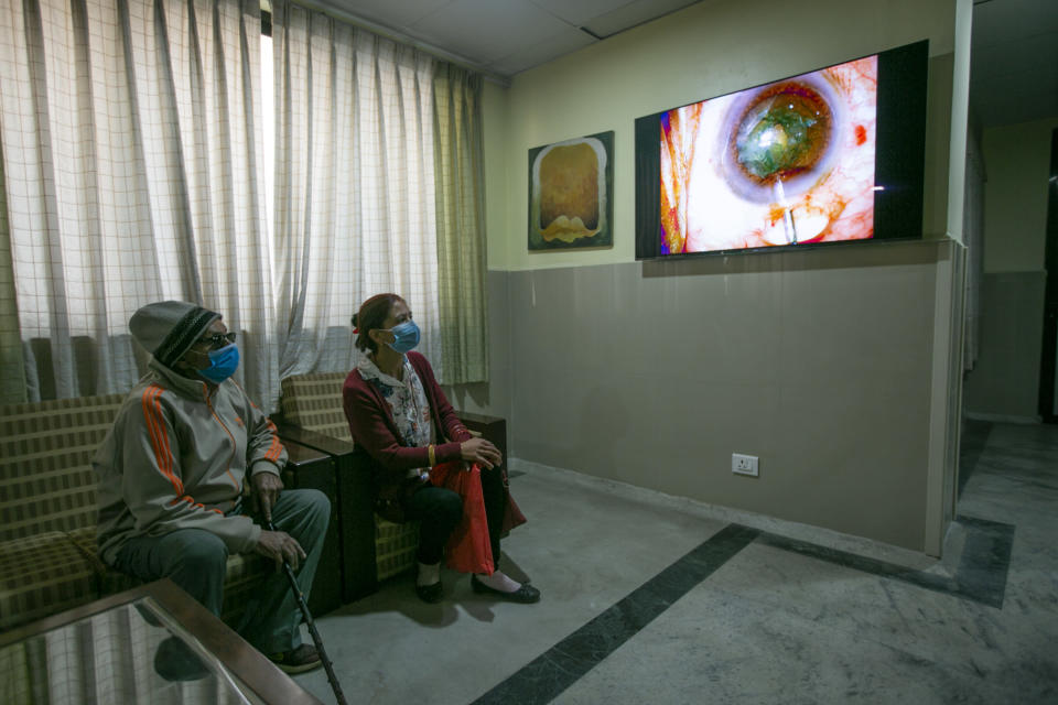 """An elderly Nepalese patient, left watches a live feed as Dr. Sanduk Ruit performs cataract surgery at the Tilganga Eye Center in Kathmandu, Nepal, March 26, 2021. Nepal's """"God of Sight"""" eye doctor renowned for his innovative and inexpensive cataract surgery for the poor is taking his work beyond the Himalayan mountains to other parts of the world so there is no more unnecessary blindness in the world. Ruit, who has won many awards for his work and performed some 130,000 cataract surgery in the past three decades, is aiming to expand his work beyond the borders of his home country and the region to go globally. (AP Photo/Niranjan Shrestha)"""