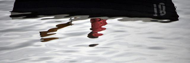 A blurred reflection of a man in a boat with a paddle.