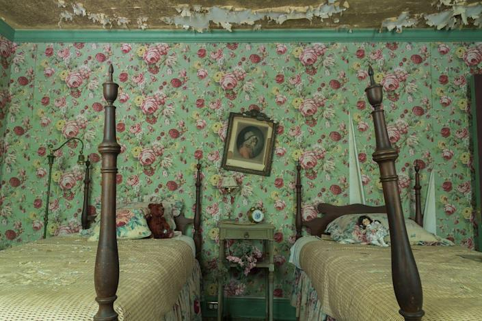 Two twin beds and floral wallpaper of an abandoned bedroom.