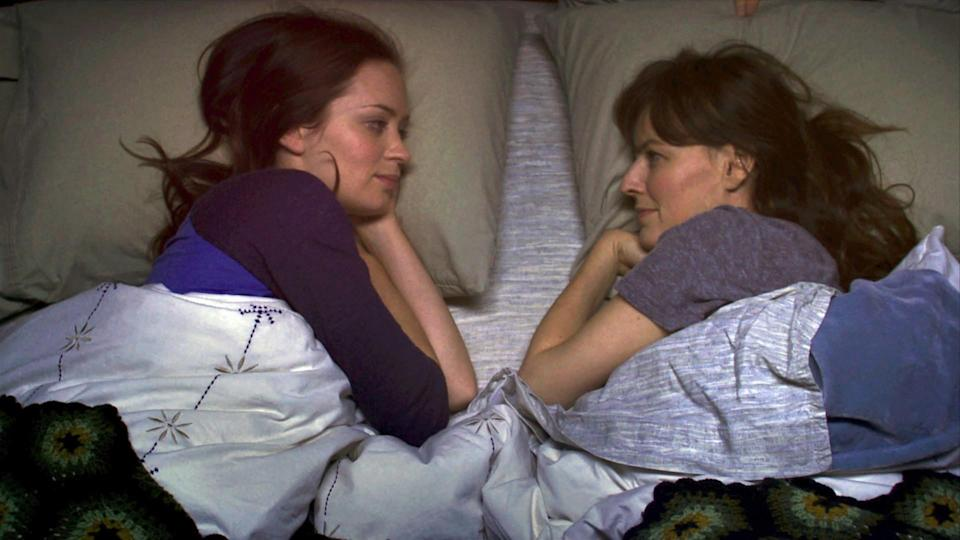 Emily Blunt and Rosemarie DeWitt staring at each other in bed.