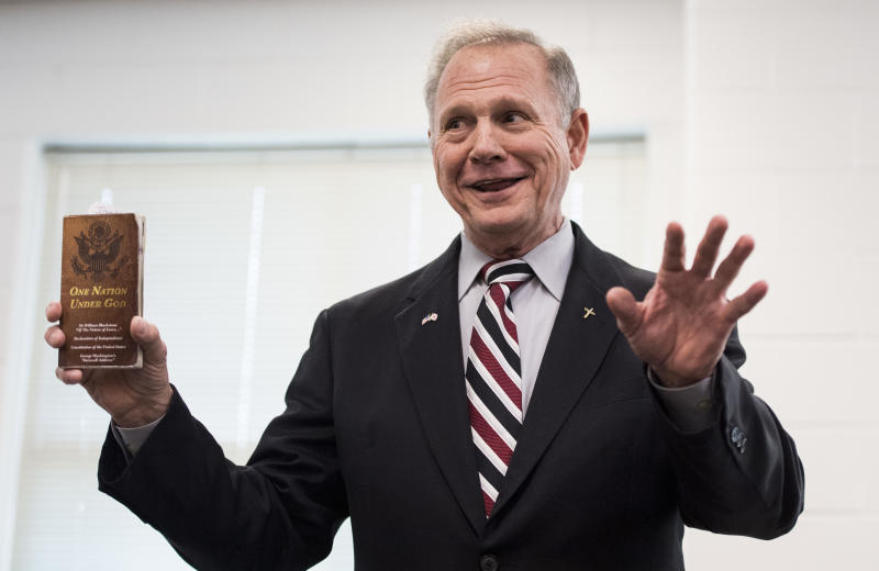 """Moore holding a """"One Nation Under God"""" pamphlet during a candidates' forum, Aug. 3. 2017. (Bill Clark via Getty Images)"""