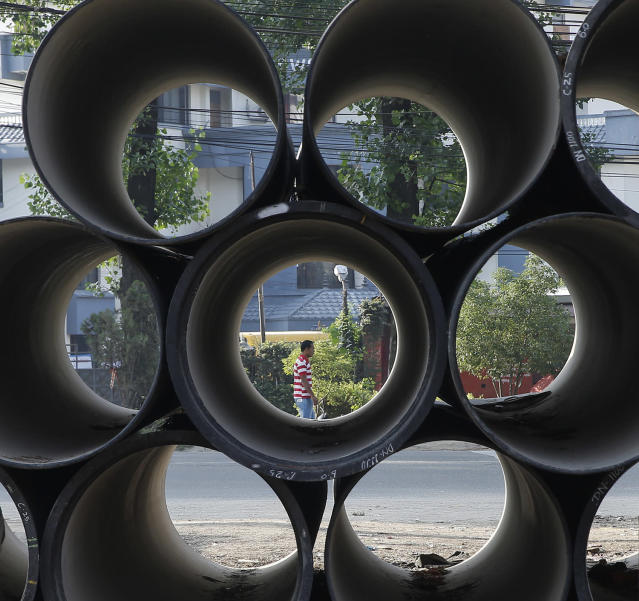 <p>A Nepalese man walks on the street seen through drinking water pipes piled at the road side in Kathmandu, Nepal, May 24, 2017. Nepal's government is replacing all underground water pipe lines in Kathmandu which is expecting to end the acute water crisis in Kathmandu. (Photo: Narendra Shrestha/EPA) </p>