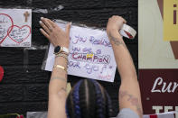 A woman tapes a message of support on a mural of Manchester United striker and England player Marcus Rashford, on the wall of the Coffee House Cafe on Copson Street, in Withington, Manchester, England, Tuesday July 13, 2021. The mural was defaced with graffiti in the wake of England losing the Euro 2020 soccer championship final match to Italy. (AP Photo/Jon Super)