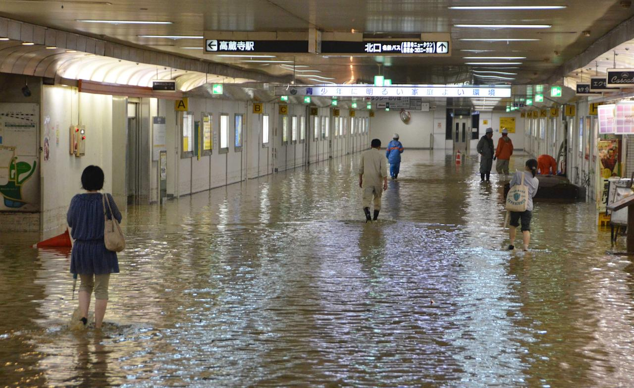 People wade through a flooded underpass of a railway station in Kasugai, central Japan Tuesday, Sept. 20, 2011. More than a million people in central Japan were urged to evacuate Tuesday as a powerful typhoon approached, triggering floods. (AP Photo/Kyodo News) JAPAN OUT, MANDATORY CREDIT, NO LICENSING IN CHINA, FRANCE, HONG KONG, JAPAN AND SOUTH KOREA