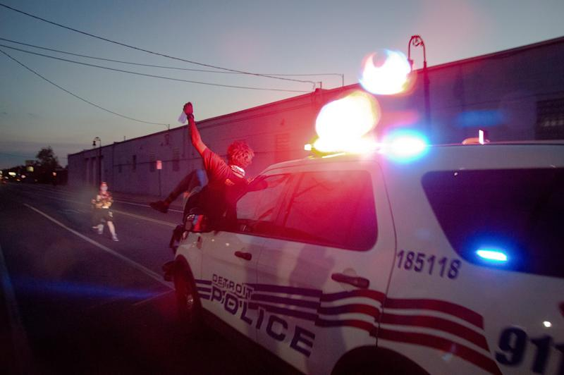 A protester is shown on the hood of a Detroit Police Department SUV before being thrown from the vehicle on Vernor Highway on Sunday, June 29.