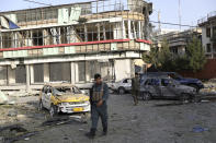 An Afghan security person walks around debris following an attack in Kabul, Afghanistan, Wednesday, Aug. 4, 2021. A powerful explosion rocked an upscale neighborhood of Afghanistan's capital Tuesday in an attack that apparently targeted the country's acting defense minister. (AP Photo/Rahmat Gul)