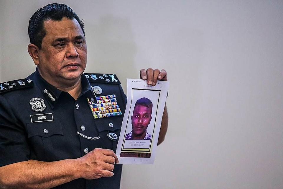Bukit Aman CID director Datuk Huzir Mohamed holds up a poster showing the suspect wanted by the police during a press conference in Kuala Lumpur December 1, 2020. — Picture by Hari Anggara