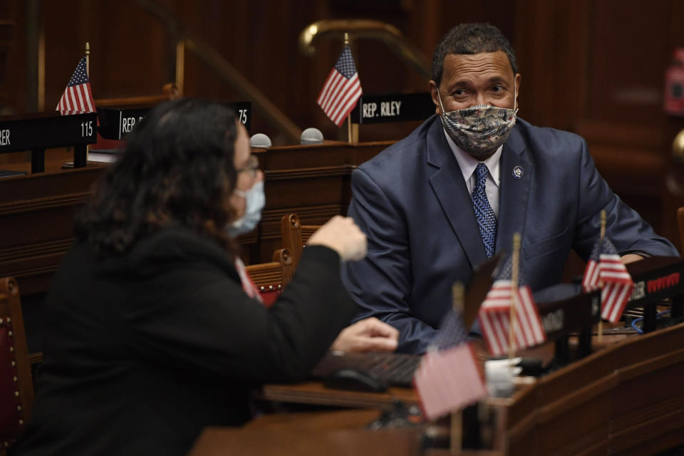State Rep. Hilda Santiago, D-Meriden, left, talks with Rep. Larry Butler, D-Waterbury, right, during session at the State Capitol in Hartford, Conn., on Monday, April 19, 2021. In July 2020 after George Floyd was killed in Minneapolis, Black and Latino members of the Connecticut General Assembly worked to enact sweeping changes to policing in the state, and since, have continue to flex their collective muscles. (AP Photo/Jessica Hill)