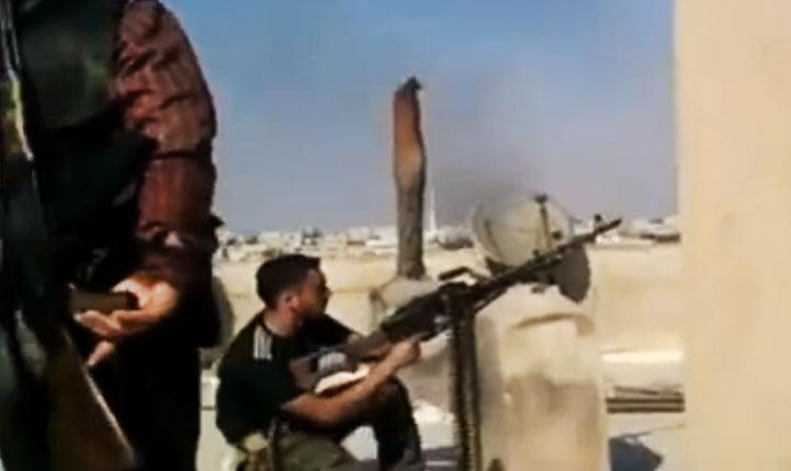 In this image made from amateur video released by the Ugarit News and accessed Tuesday, July 24, 2012, a Free Syrian Army solider fires his weapon during clashes with Syrian government troops in Aleppo, Syria. Turkey sealed its border with Syria to trucks on Wednesday, July 25, 2012 cutting off a vital supply line to the embattled nation as fighting stretched into its fifth day in the commercial capital of Aleppo. (AP Photo/Ugarit News via AP video) TV OUT, THE ASSOCIATED PRESS CANNOT INDEPENDENTLY VERIFY THE CONTENT, DATE, LOCATION OR AUTHENTICITY OF THIS MATERIAL