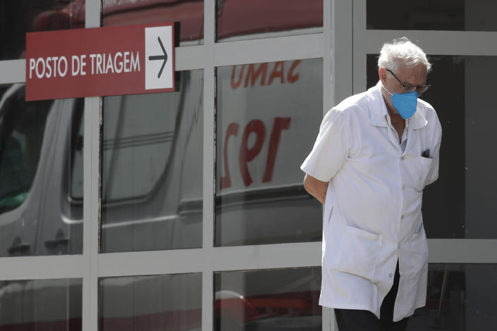 A doctor gets some fresh air as he takes a walk outside the HRAN Hospital in Brasilia, Brazil, Wednesday, March 3, 2021. The number of new COVID-19 cases in Brazil is still surging, with a new record high of deaths reported on Tuesday. (AP Photo/Eraldo Peres)