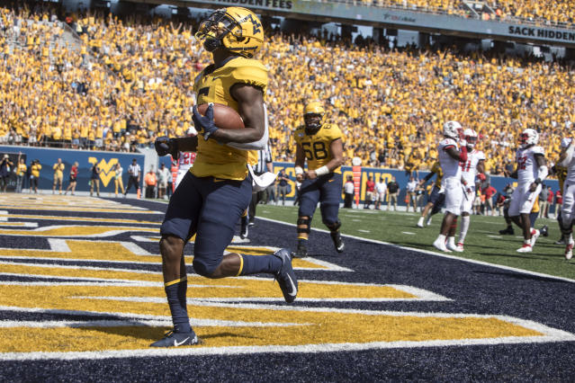 West Virginia running back Kennedy McKoy (6) runs for a touchdown during the second half of an NCAA college football game against North Carolina State Saturday, Sept. 14, 2019, in Morgantown, W.Va. (AP Photo/Raymond Thompson)