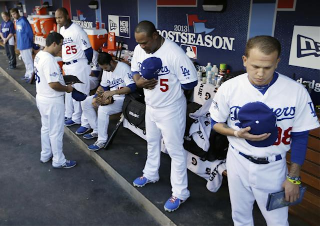 Los Angeles Dodgers players pause for a moment of silence for umpire Wally Bell before Game 4 of the National League baseball championship series against the St. Louis Cardinals, Tuesday, Oct. 15, 2013, in Los Angeles. (AP Photo/David J. Phillip)