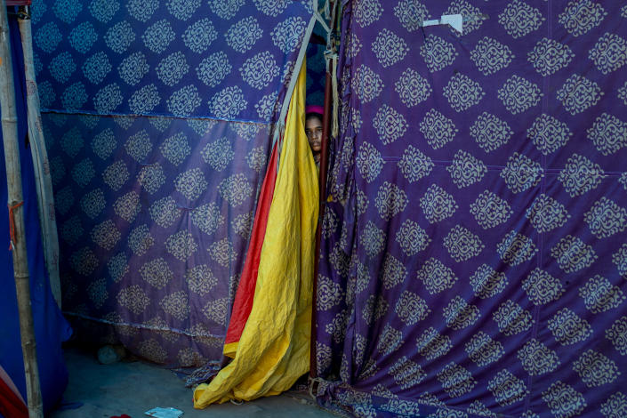 A Rohingya refugee woman peeps out from her tent at a refugee camp alongside the banks of the Yamuna River in the southeastern borders of New Delhi, sprawling Indian capital, July 1, 2021. Millions of refugees living in crowded camps are waiting for their COVID-19 vaccines. For months, the World Health Organization urged countries to prioritize immunizing refugees, placing them in the second priority group for at-risk people, alongside those with serious health conditions. (AP Photo/Altaf Qadri)
