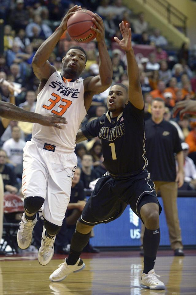 Oklahoma State's Marcus Smart (33) drives past Purdue guard Sterling Carter (1) during the first half of an NCAA college basketball game in Kissimmee, Fla., Thursday, Nov. 28, 2013. (AP Photo/Phelan M. Ebenhack)